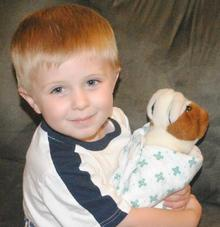 Children learn what they live: boy nurtures toy dog